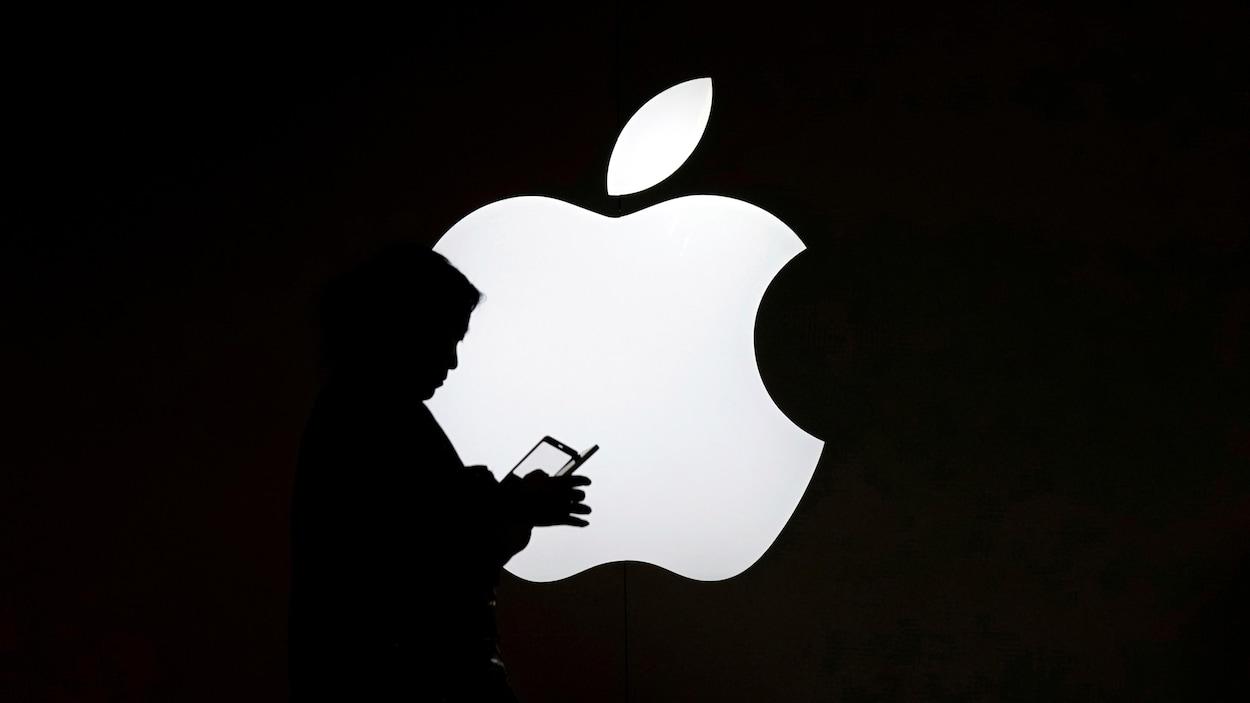Une femme regarde l'écran de son téléphone portable devant un logo Apple.