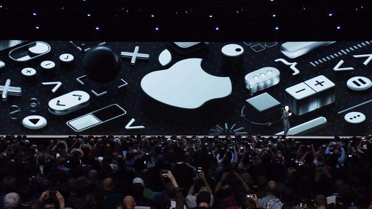 Une capture d'écran de la présentation des nouveaux logiciels d'Apple montrant une vue d'ensemble de la salle, avec un énorme écran sur la scène, derrière Tim Cook.