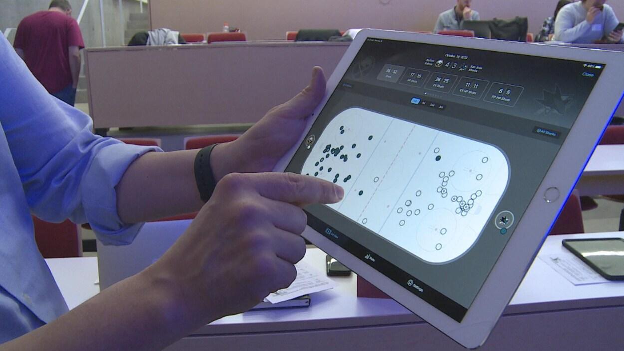 Un homme pointe quelque chose sur une tablette électronique.