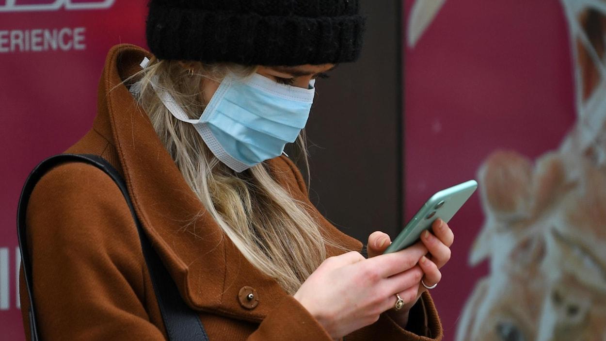 Une femme coifée d'une tuque en laine et le visage recouvert d'un masque médical est penchée sur son téléphone cellulaire.