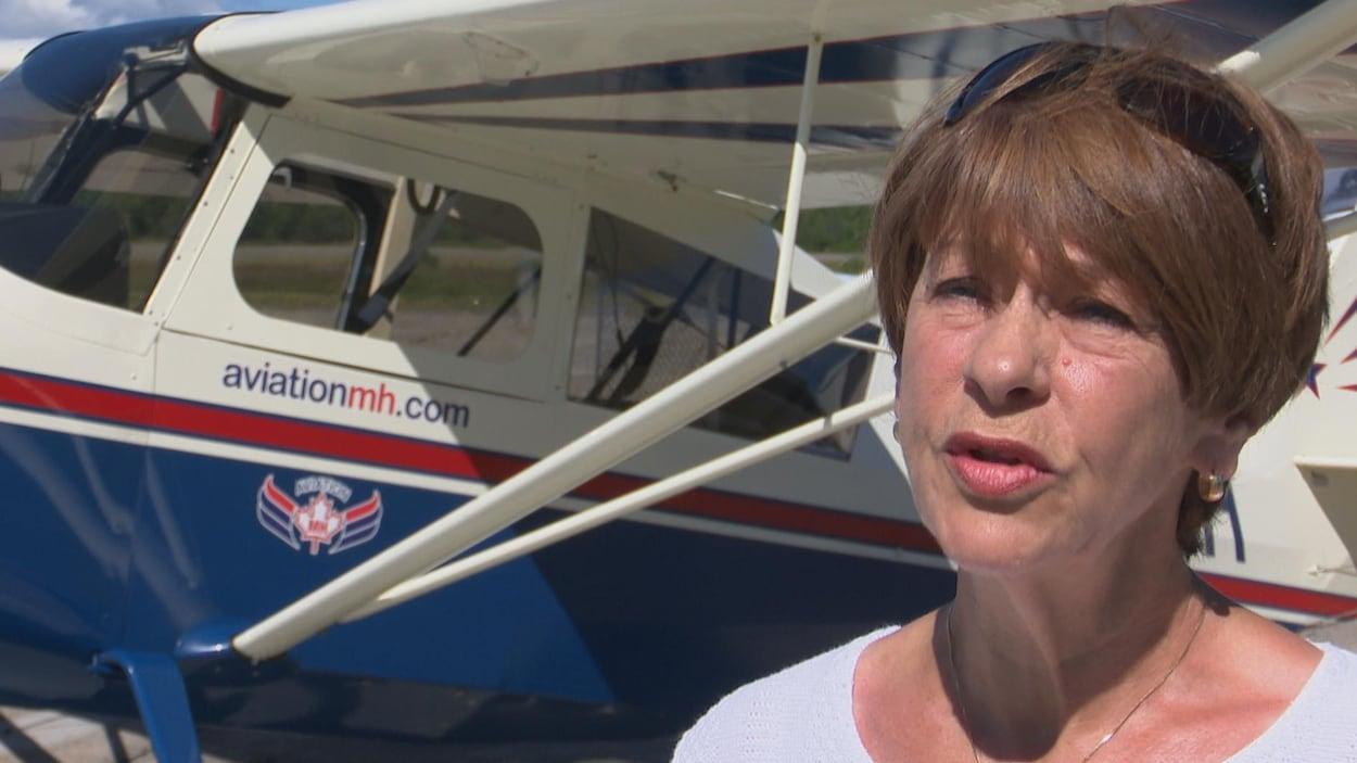 Françoise Sasseville témoigne devant l'avion qu'elle apprend à piloter.