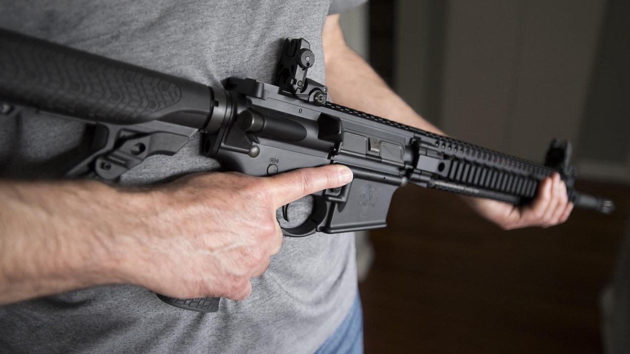 Un homme tient une arme AR-15 dans ses mains.
