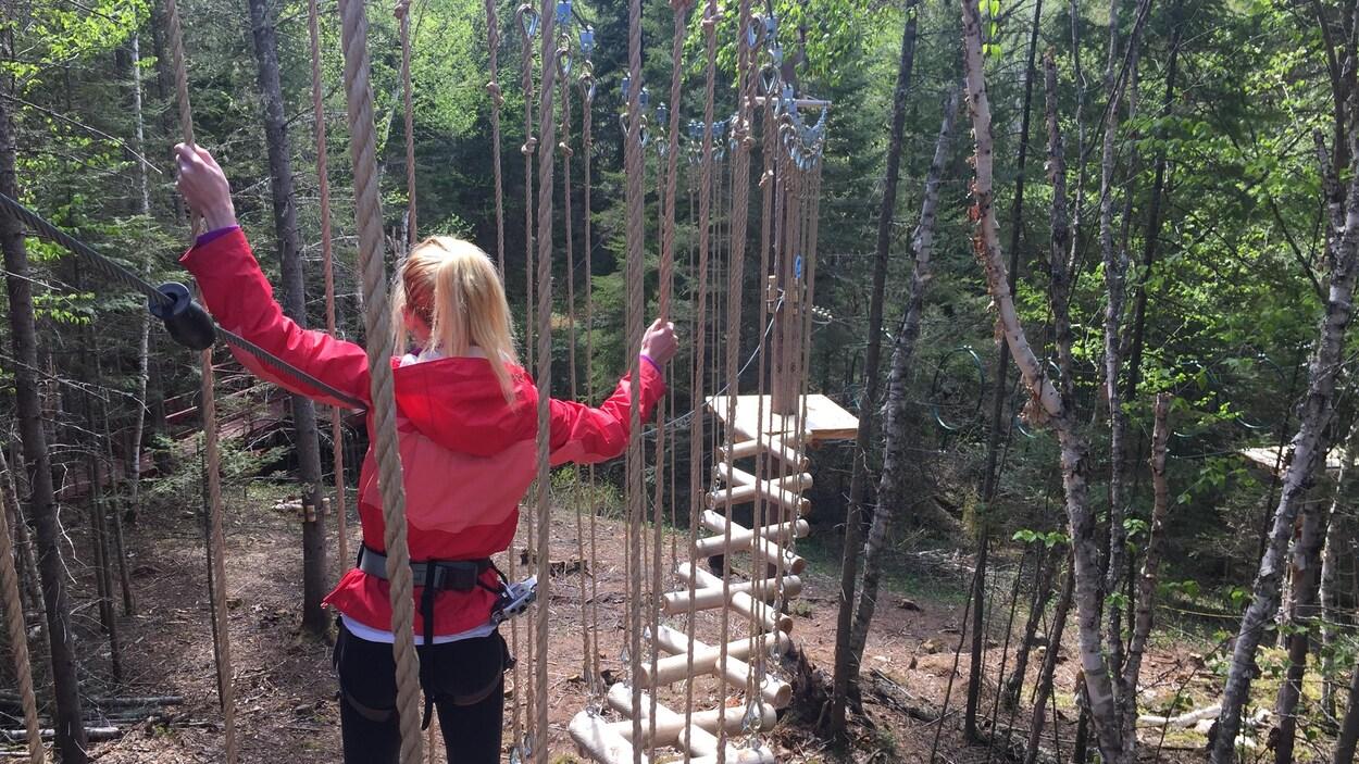 Une femme marche sur des bouts de bois suspendus par des cordes.