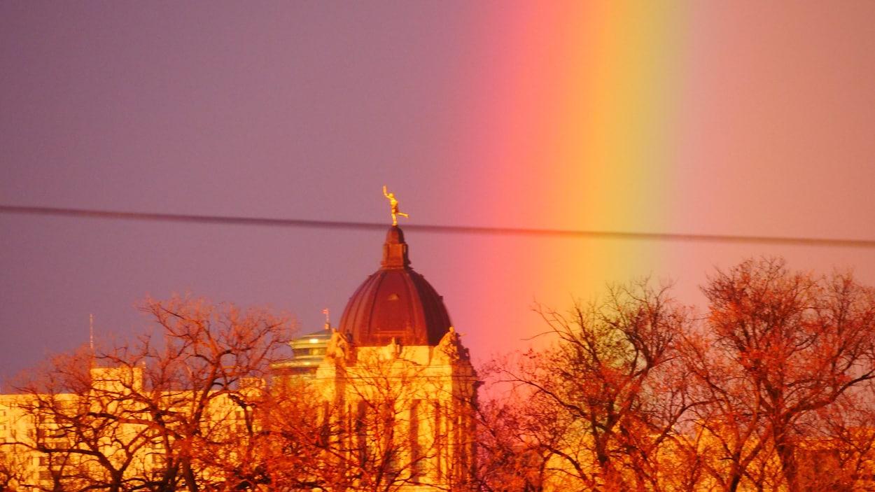 Un arc-en-ciel côtoie le haut du palais législatif que surplombe la statue du Golden Boy.