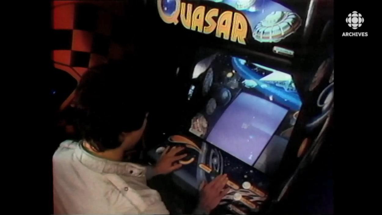 Un jeune homme joue au jeu vidéo Quasar dans une arcade.