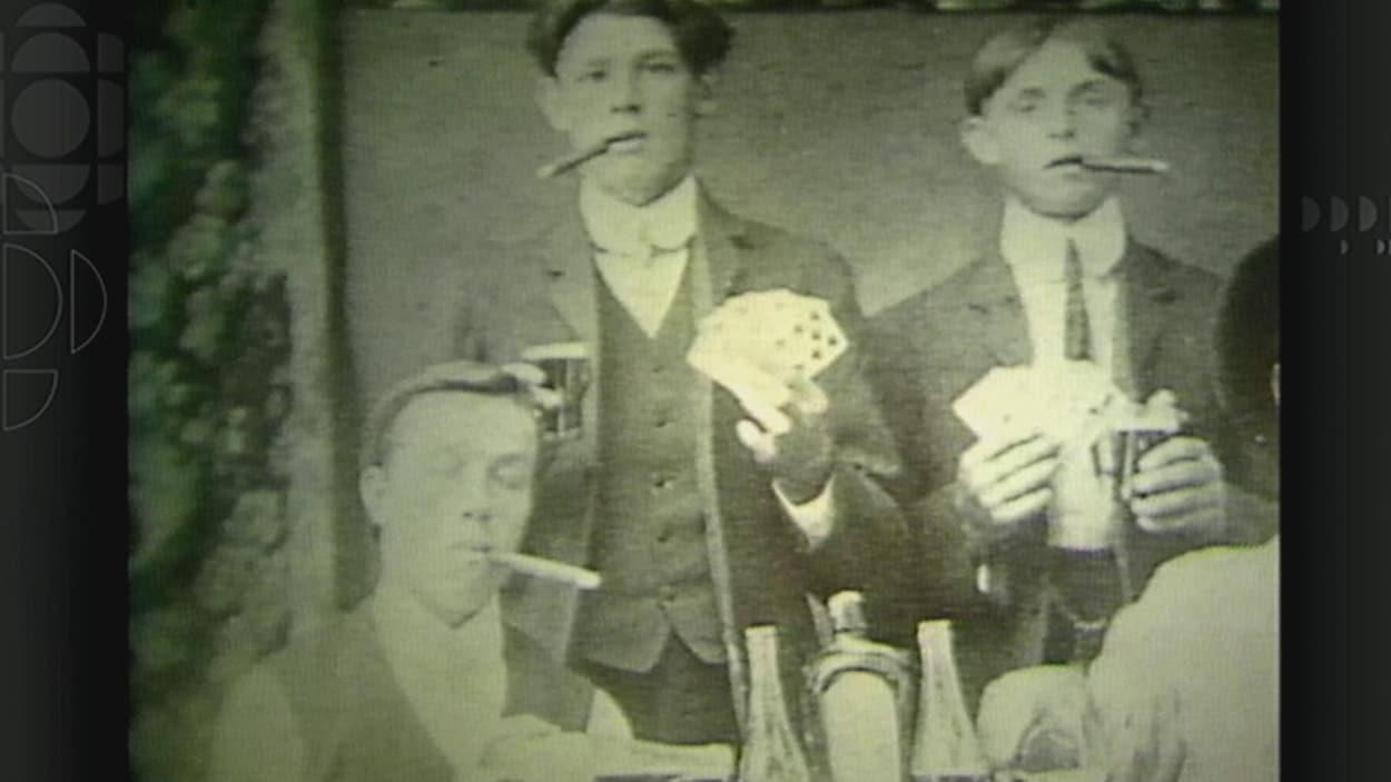 Des jeunes qui fument des cigars et jouent aux cartes