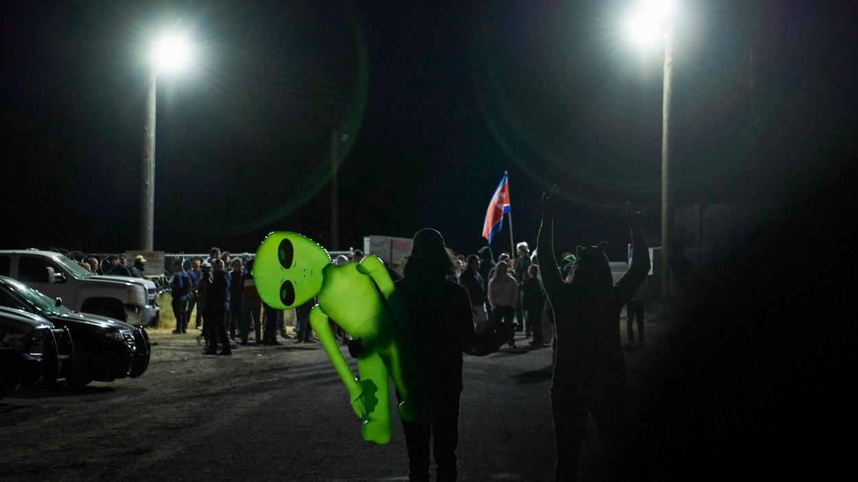 Quelques dizaines de personnes, certaines déguisées, l'une portant un jouet gonflable d'extraterrestre vert, se tiennent devant une barrière de sécurité durant la nuit.