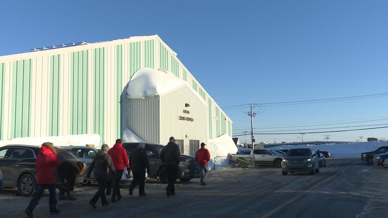 Des personnes marchent dans le stationnement vers l'entrée de l'aréna, en hiver.