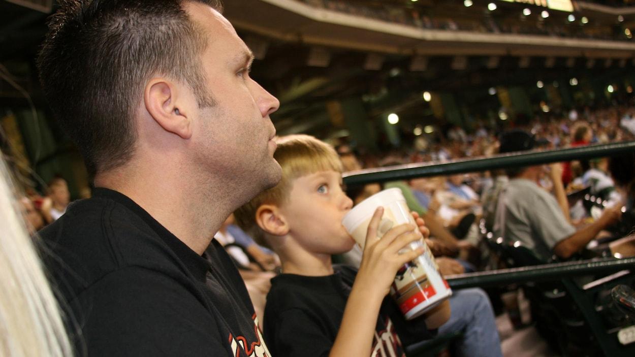 Un père et son fils dans les gradins d'un aréna, l'enfant boit une boisson sucrée