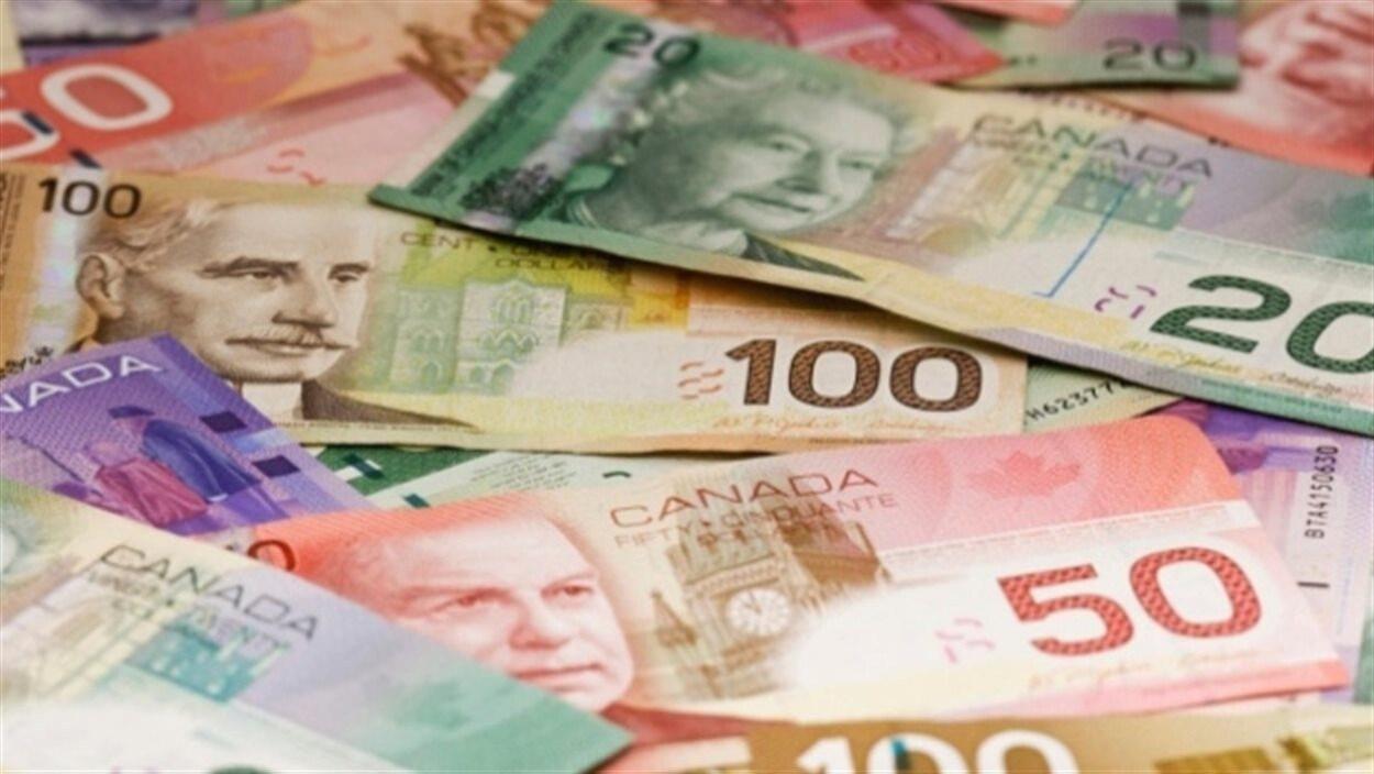 Des billets de banque de toutes les couleurs éparpillés sur le sol.