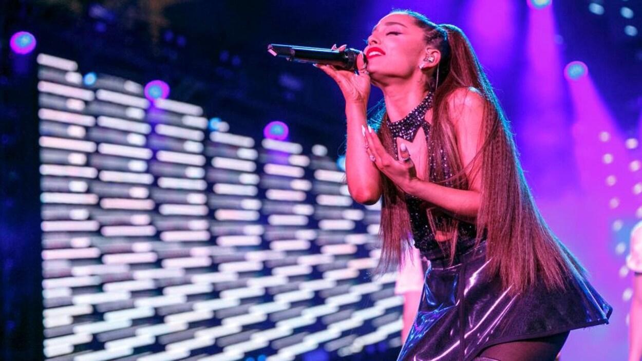 Portrait d'Ariana Grande qui chante sur scène.