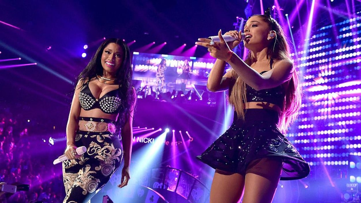 Nicki Minaj tient un micro et Ariana Grande chante.