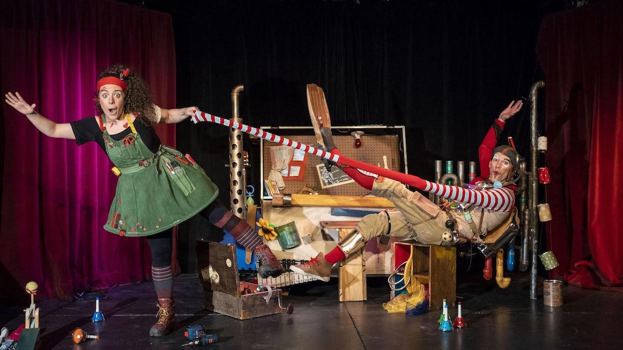Scène humoristique lors d'un spectacle pour enfants. Une femme en costume tire sur la manche à rallonge d'un homme, lui aussi en costume.