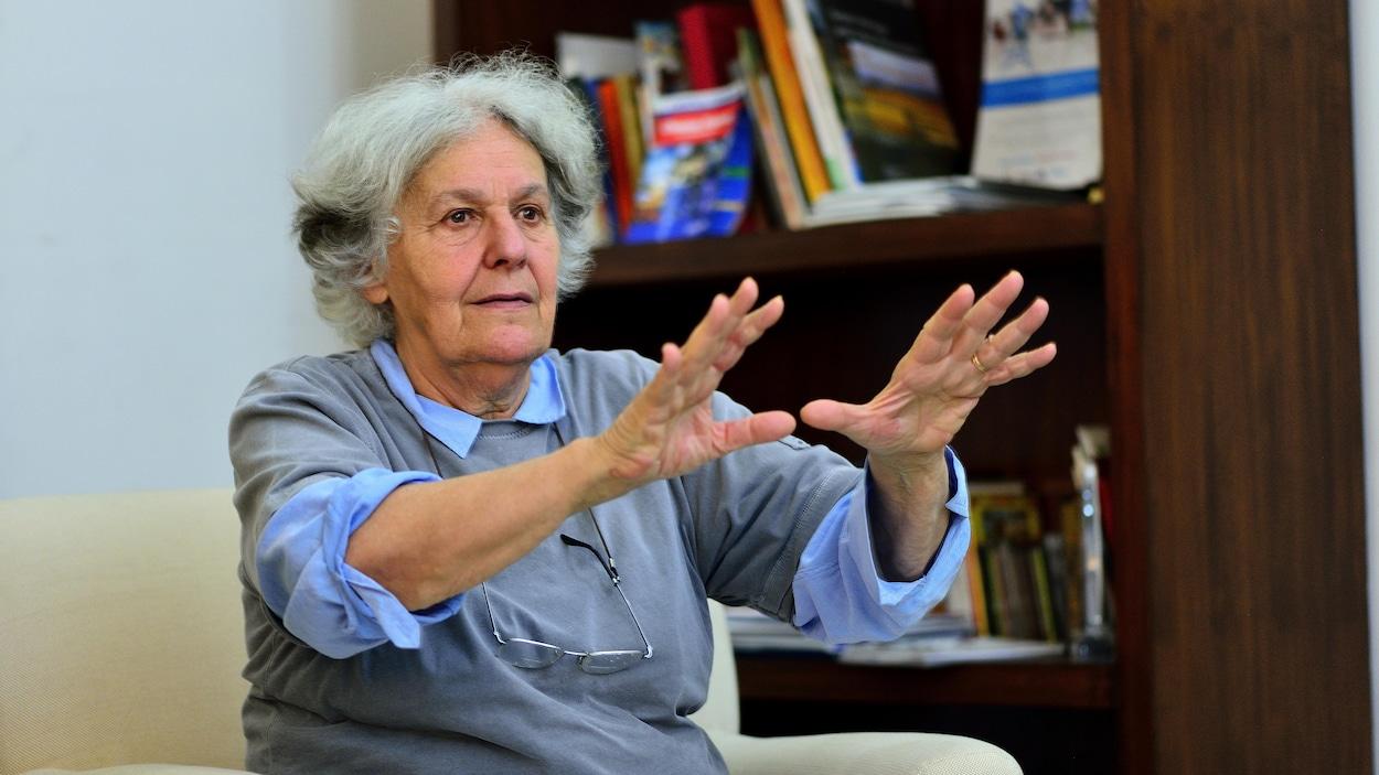 La fondatrice du Théâtre du Soleil, Ariane Mnouchkine, tend les mains, en parlant, assise sur un fauteuil.