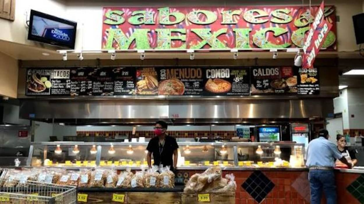 Des travailleurs et des clients dans un supermarché hispanique.