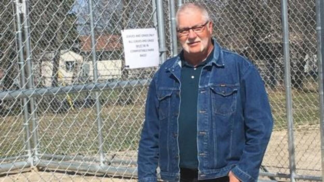 Un homme est debout à côté d'une grande cage.