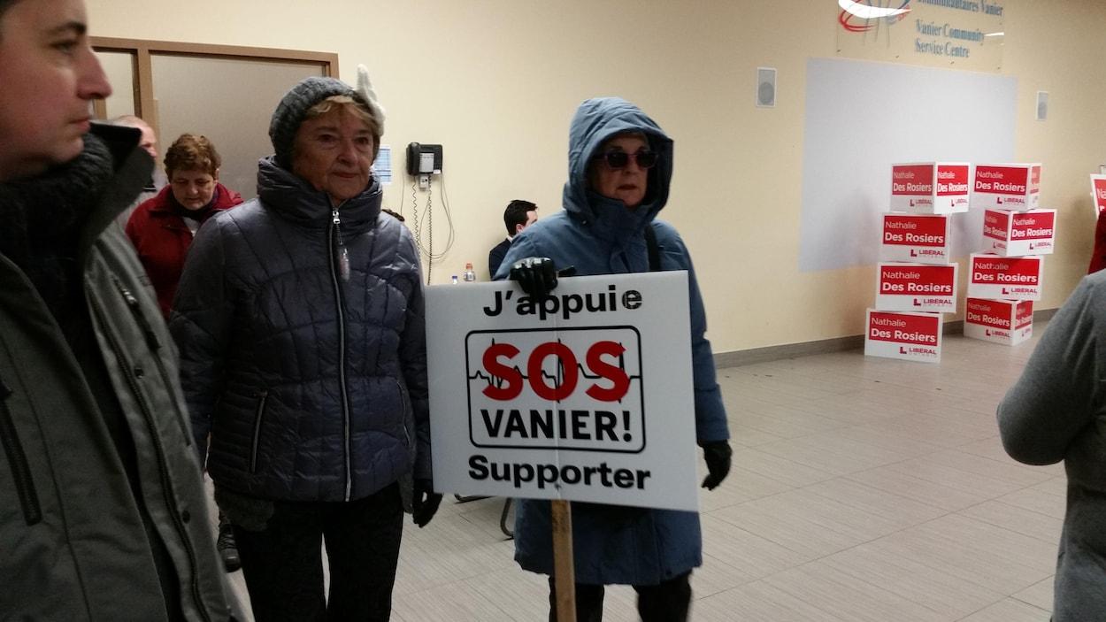 Des gens à l'intérieur d'un centre communautaire. Une femme tient une affiche « J'appuie SOS Vanier ».