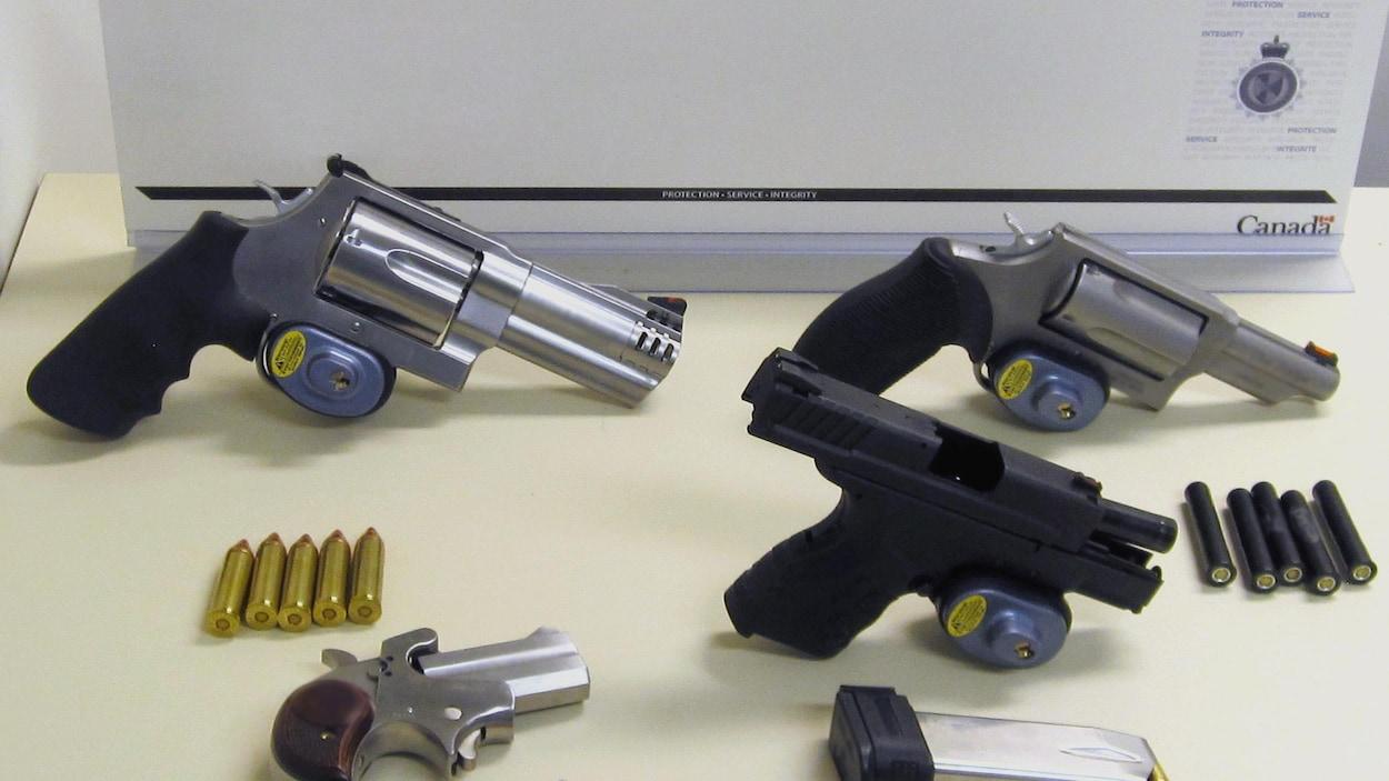 Quatre revolvers et pistolets sur une table.