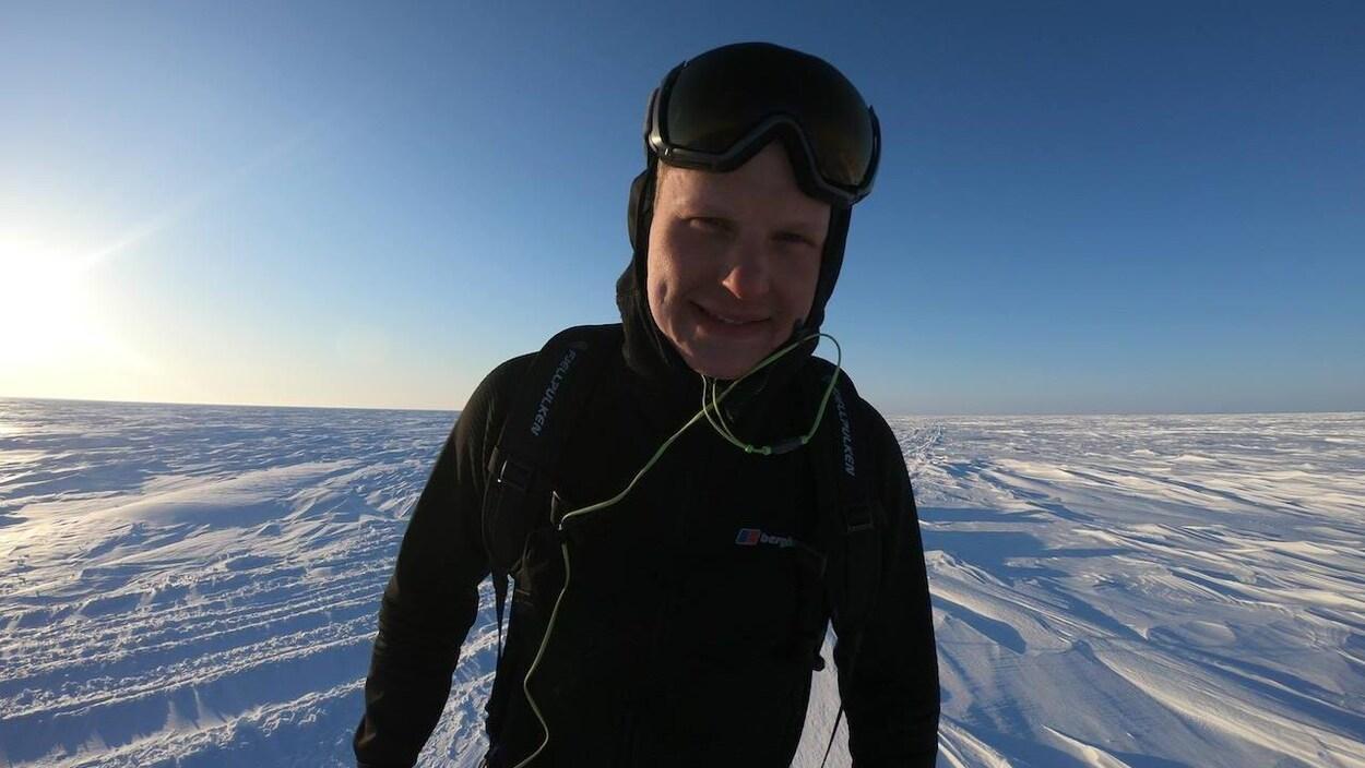 Un homme avec des lunettes de ski debout dans la neige.