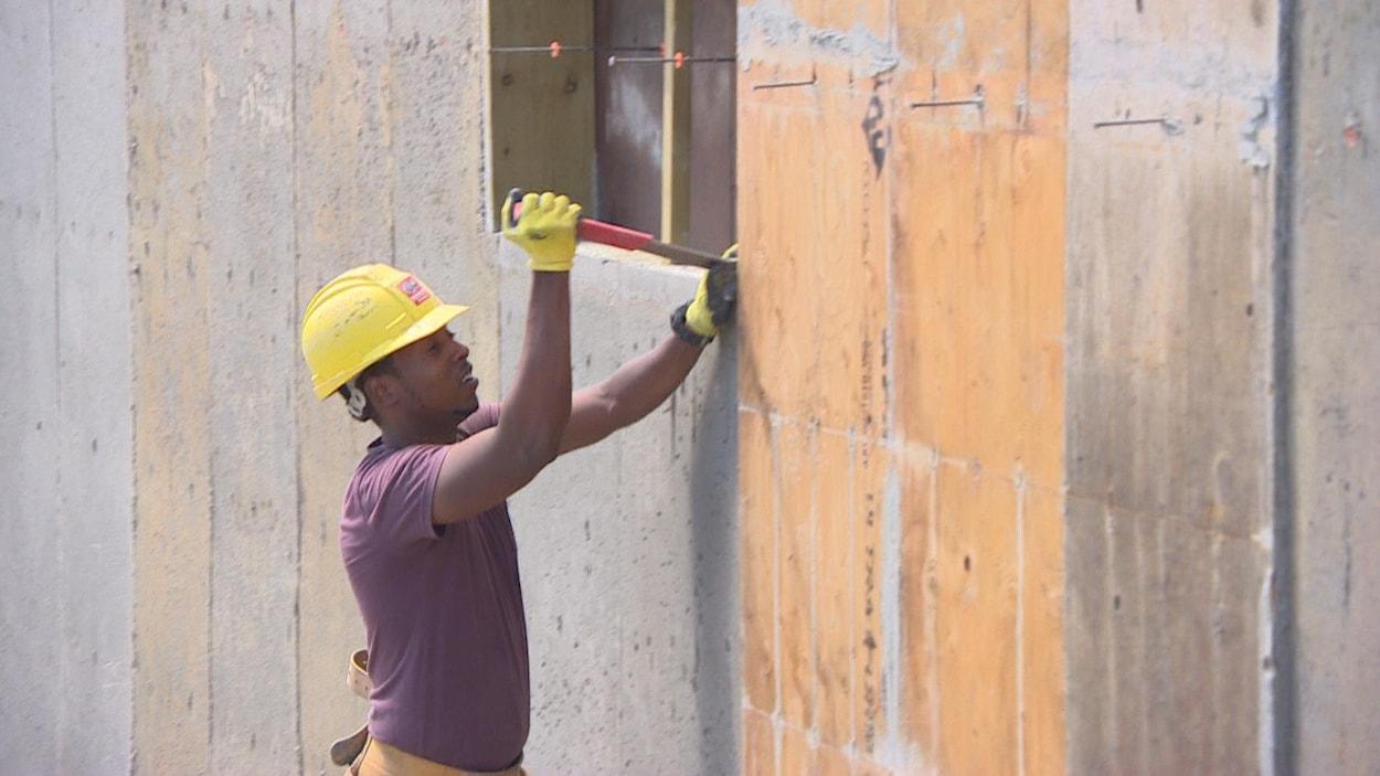 Un homme portant un casque de construction et des gants enlève le coffrage d'une fondation à l'aide d'un marteau.