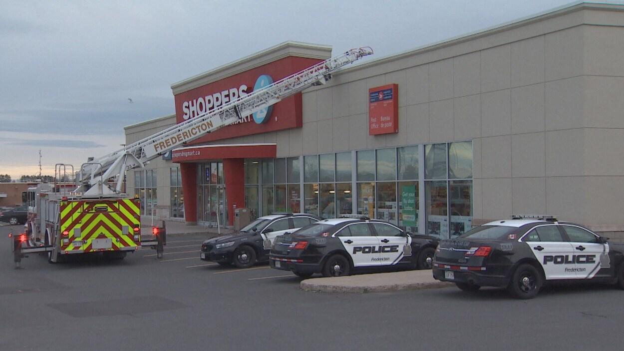 Des voitures de police sont stationnées devant un Shoppers Drug Mart. Le véhicule des pompiers est également sur place.