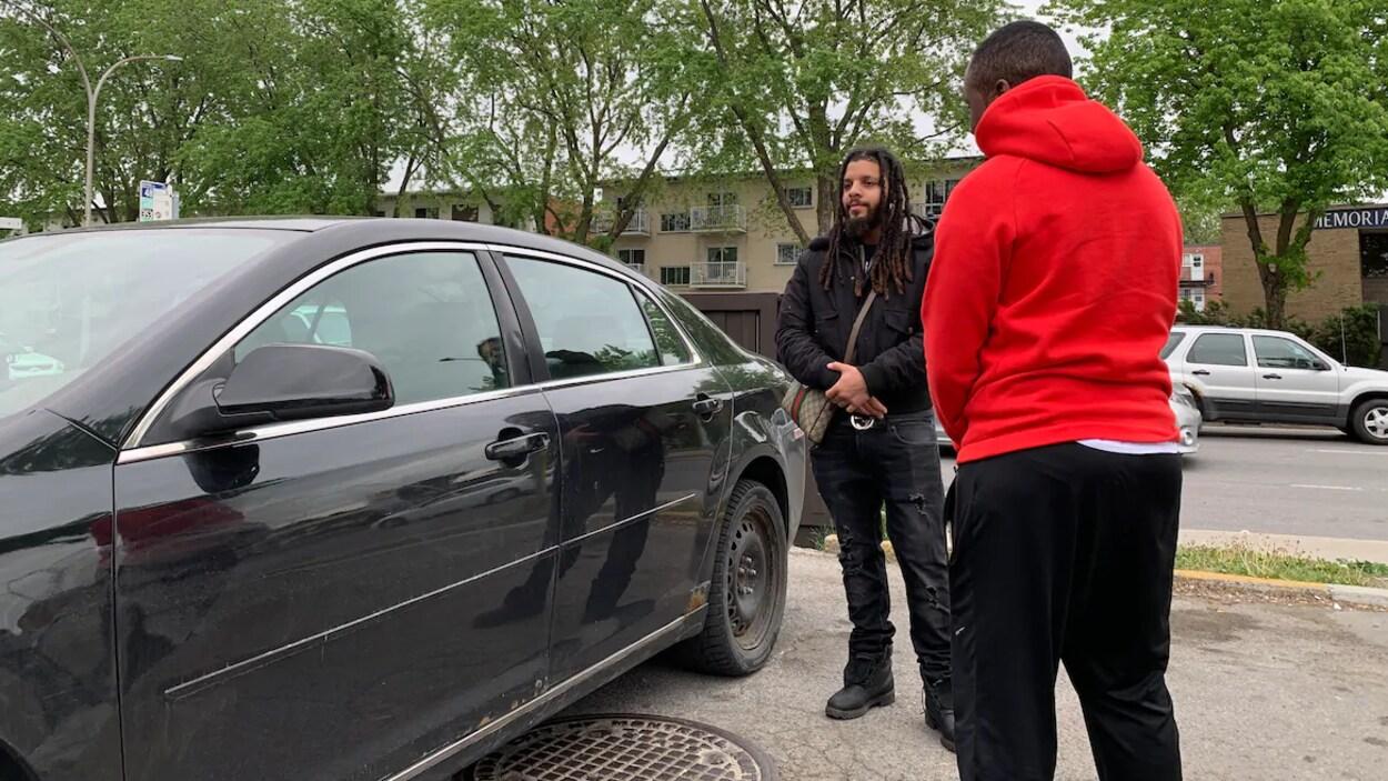 Deux jeunes hommes se trouvent près d'une voiture.
