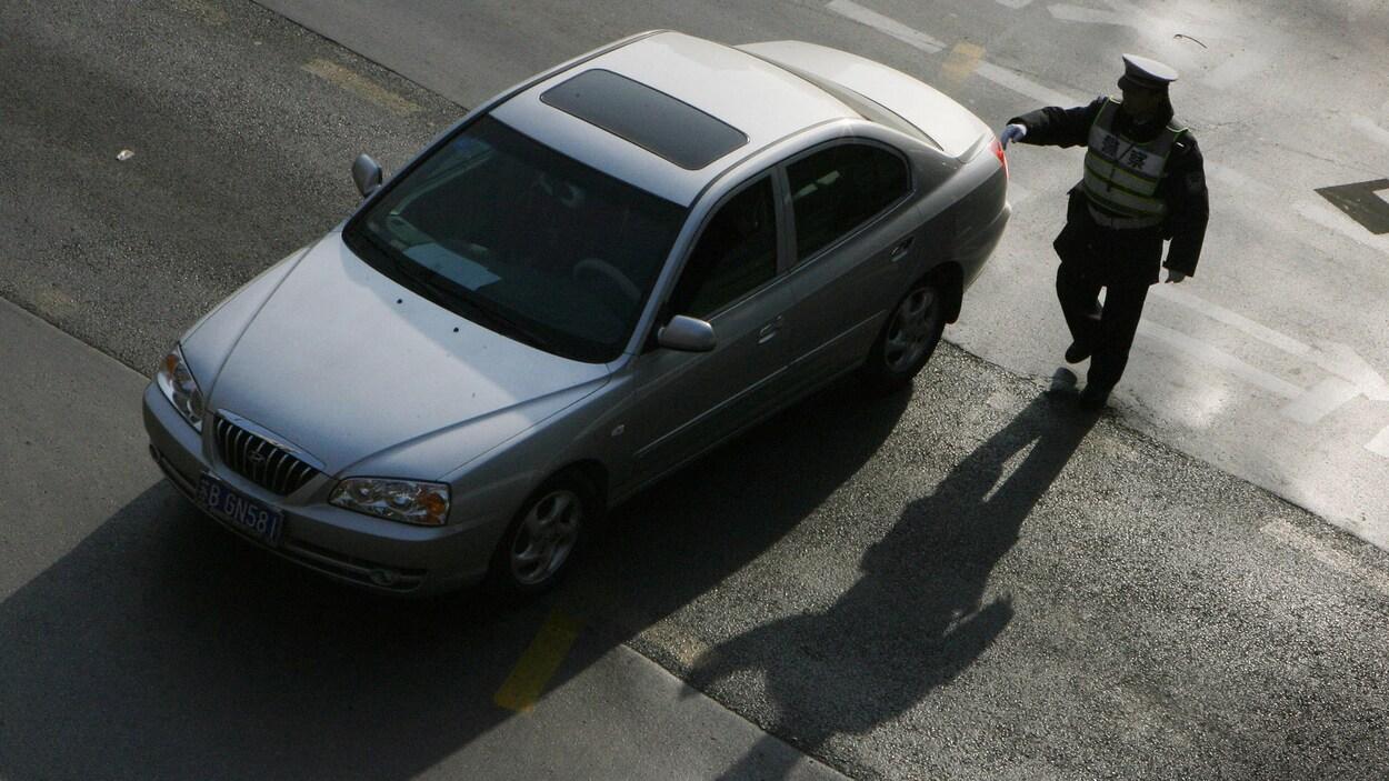 Un policier arrête un automobiliste.
