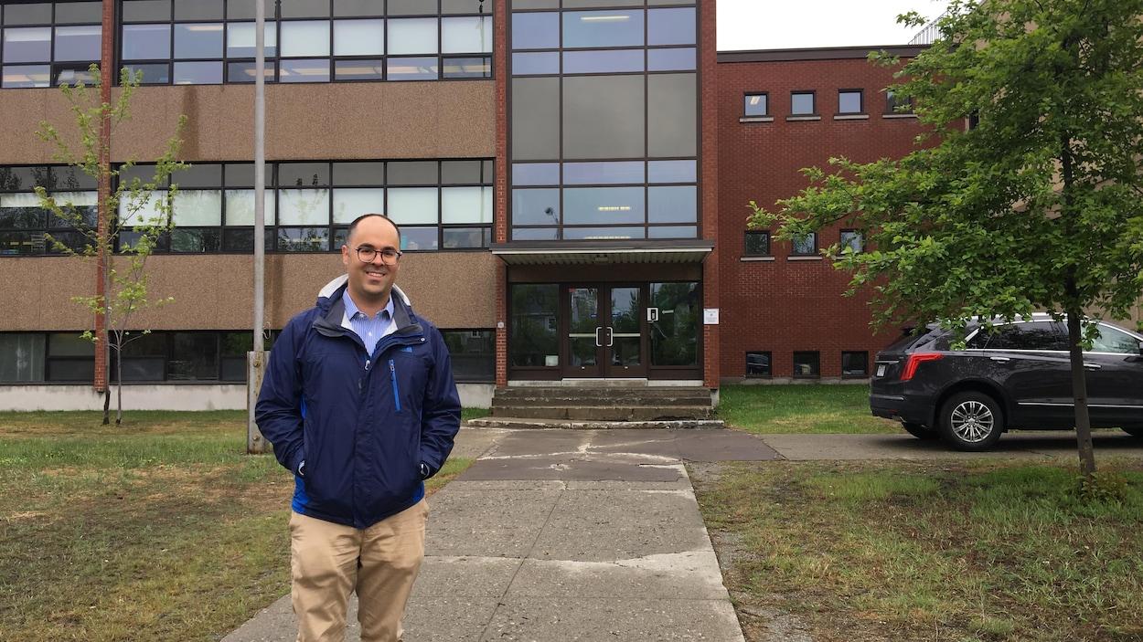 Un homme sourit à la caméra devant un établissement scolaire.