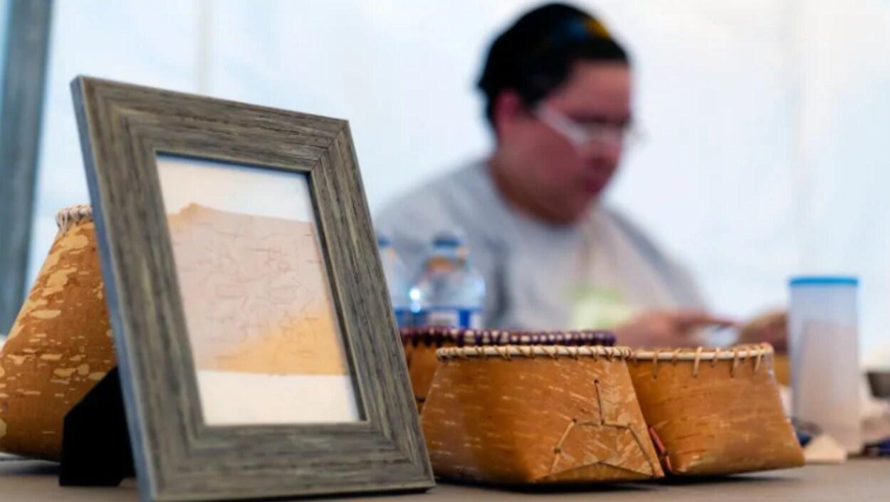Une femme en arrière plan. Sur la table devant elle, des paniers en écorce de bouleau et un cadre en bois.