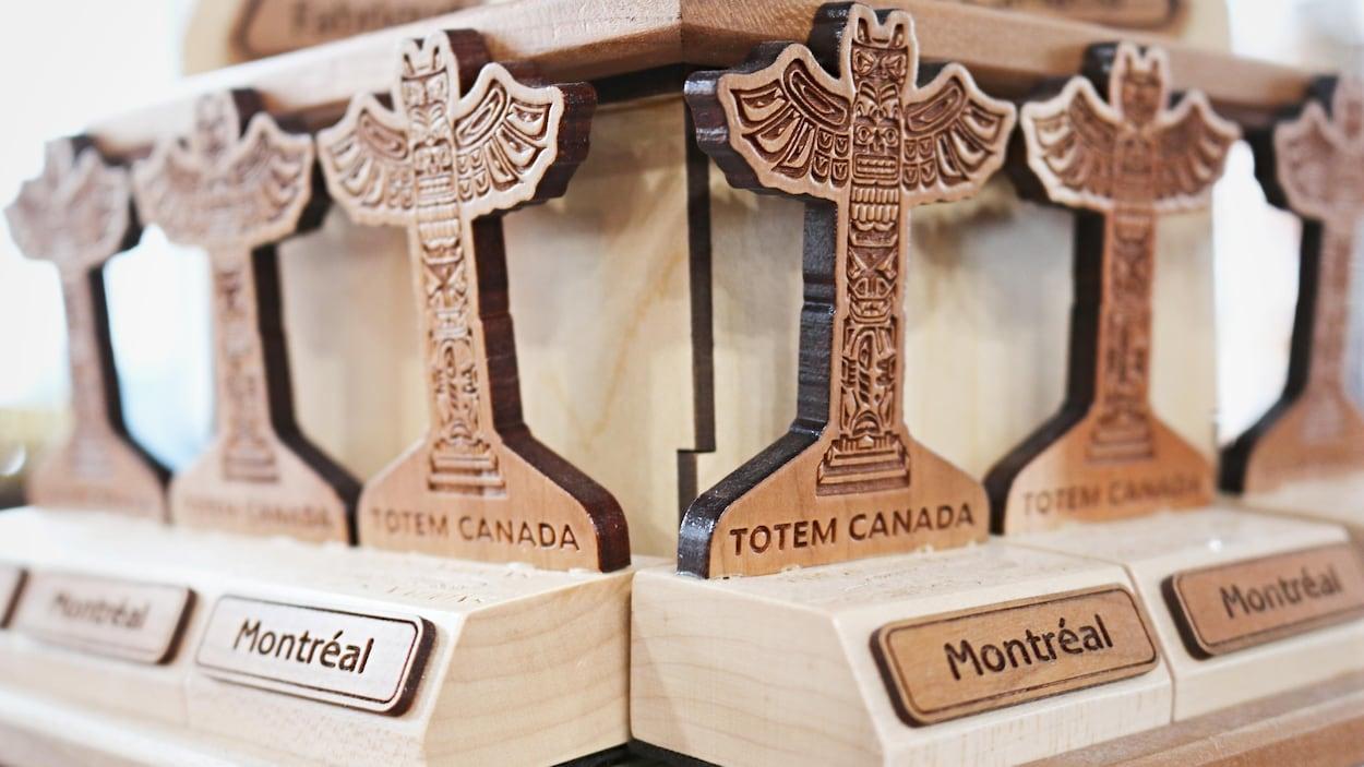 Une série de petites statuettes de bois en forme de totems sont posées sur l'étagère d'une boutique de souvenirs du Vieux-Port de Montréal.