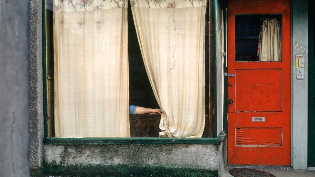 Une photo colorée montrant un bras qui tire un rideau de fenêtre. Il y a une porte rouge.