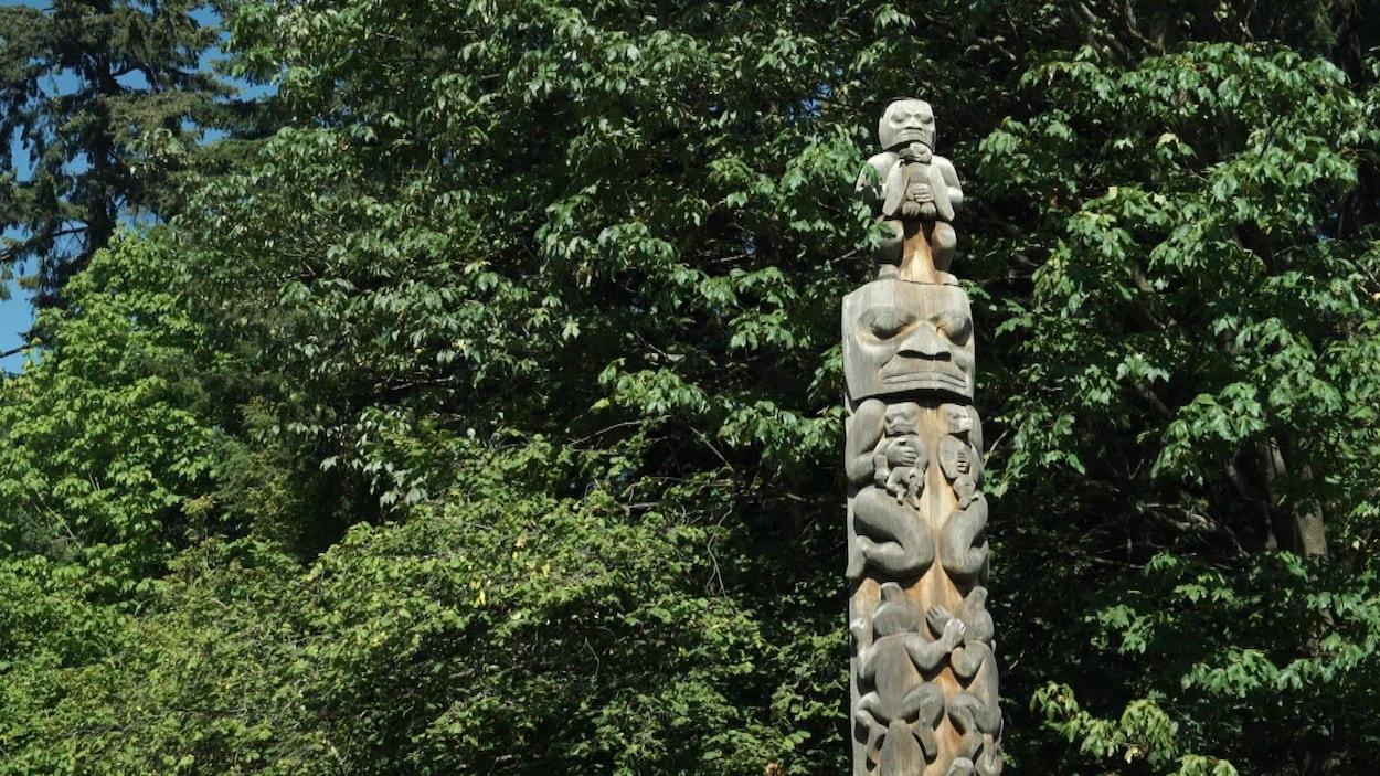 Totem sculpté sur bois, avec en arrière-plan des arbres touffus.