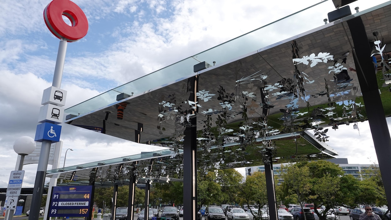 Des fleurs de métal découpées d'un plafond métallique suspendues au-dessus d'un trottoir à la station Tremblay du train léger d'Ottawa.