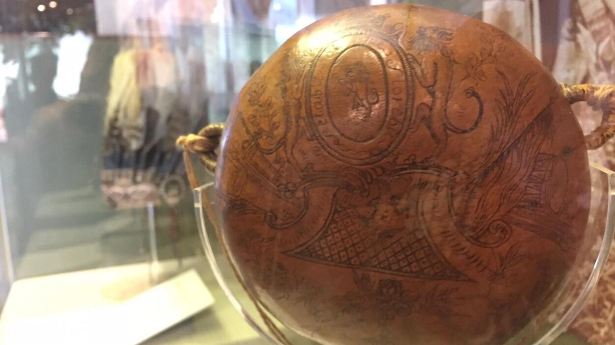 Un objet rond et brun qui ressemble à de la poterie a des motifs noirs dessinés dessus.