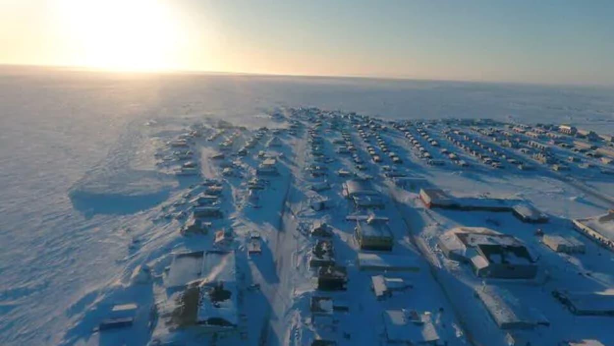 La communauté d'Arviat sous la neige photographiée de haut en avril par un drone avec le soleil à l'horizon.