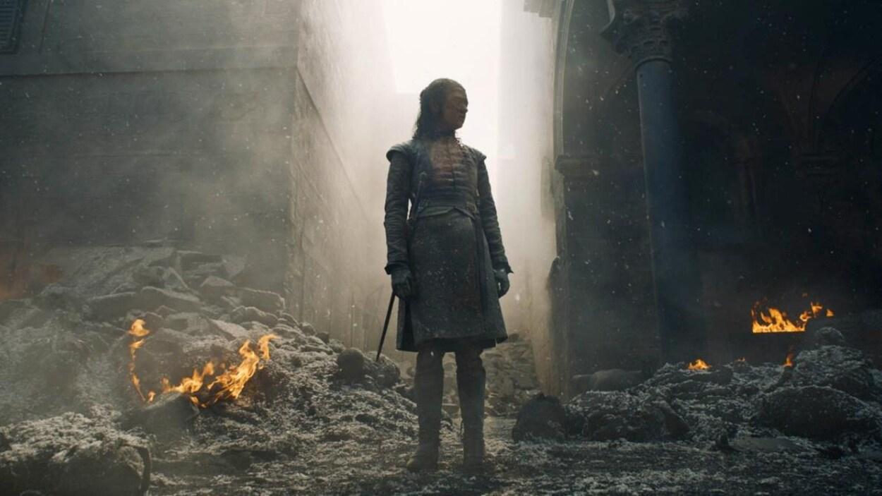 Le personnage d'Arya Stark, vêtue en tenue de combat, se tient au milieu de décombres et de corps calcinés.