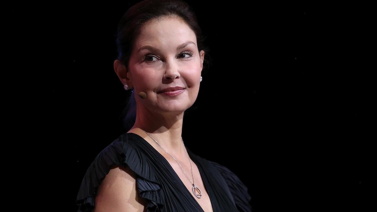 Ashley Judd, souriante sur une scène, le regard vers la gauche