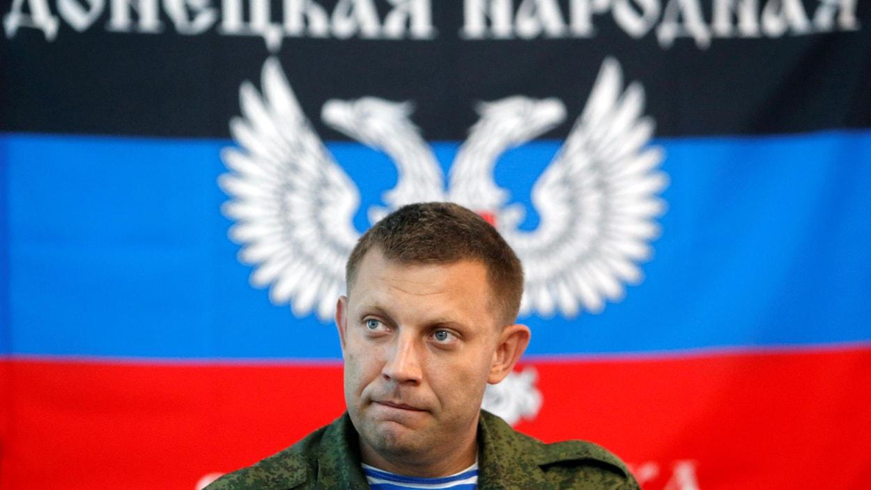Alexandre Zakhartchenko, des épaules en montant, regard sérieux, en habit militaire, devant un drapeau de sa République autoproclamée.