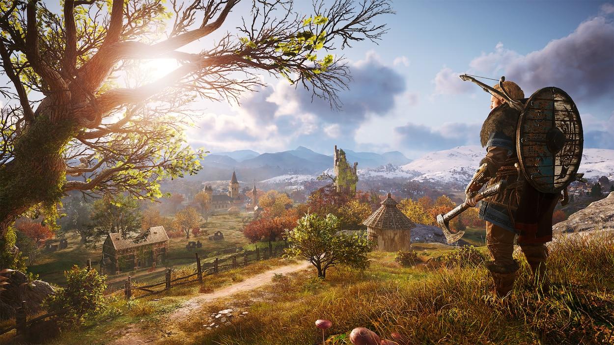Capture d'écran du jeu vidéo montrant un guerrier viking en haut d'une montagne gazonnée, avec une vue sur un village.