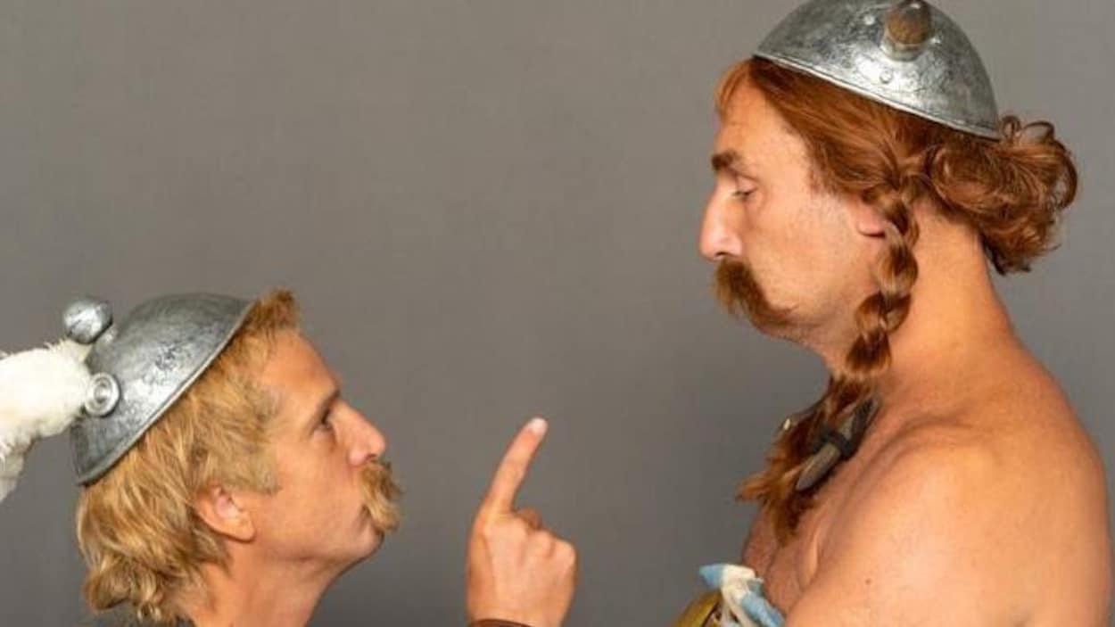 Les deux acteurs se font face et portent tous les deux une moustache.