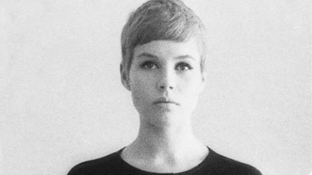 Un portrait en noir et blanc d'Astrid Kirchherr, jeune femme qui porte les cheveux courts.