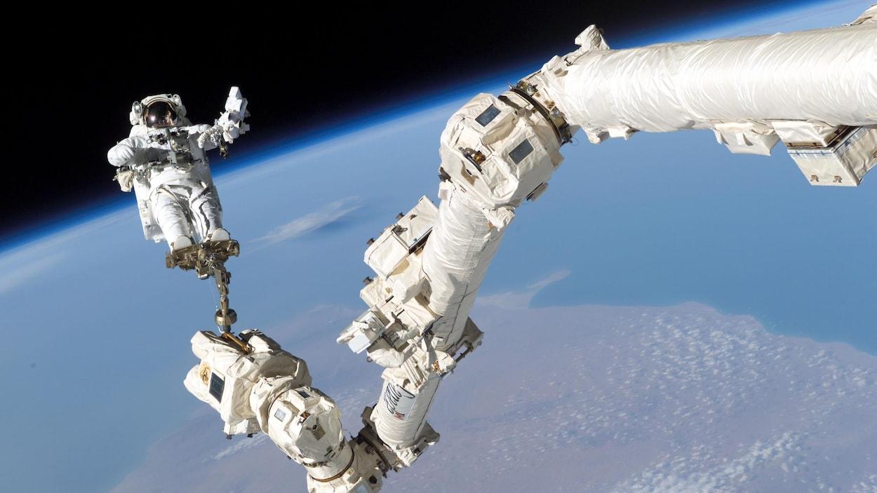 Une photo de l'astronaute américain Stephen K. Robinson perché au bout du Canadarm2 pour effectuer des travaux sur la Station spatiale internationale.