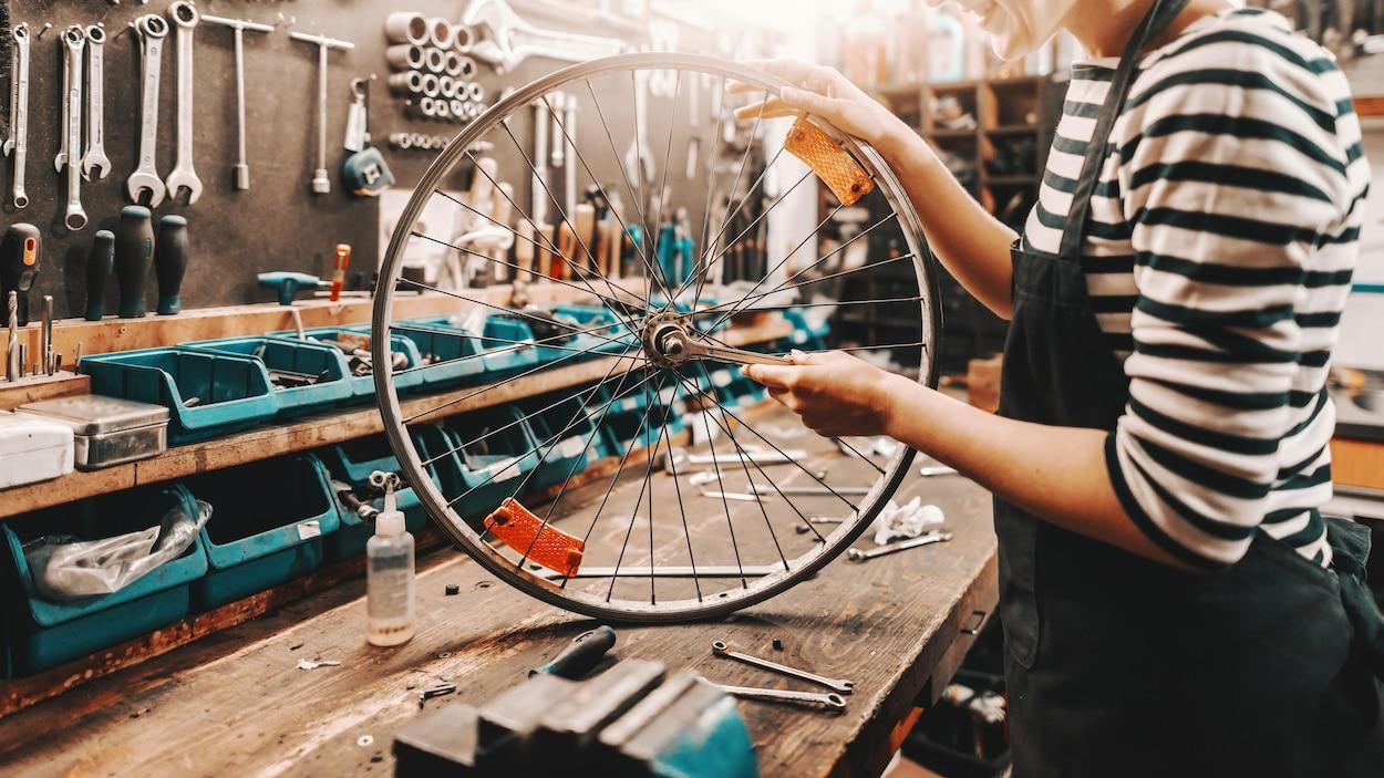 Une femme semble réparer une roue de vélo.