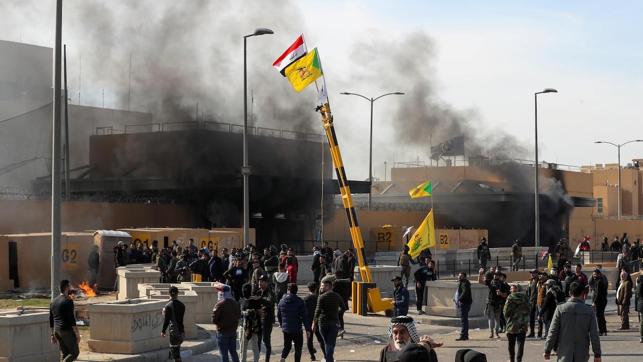 Des gens sont massés près d'un édifice d'où s'échappe de la fumée.