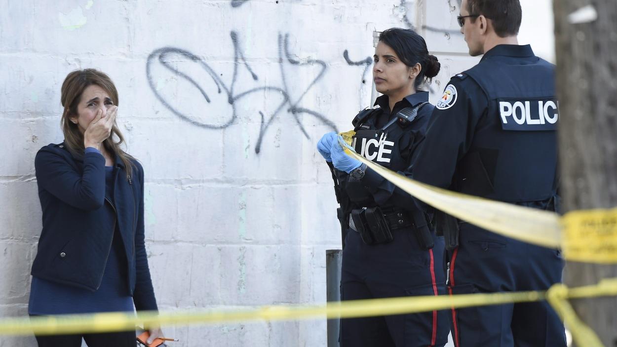 Deux policiers à côté d'une femme bouleversée qui se tient la bouche avec la main.
