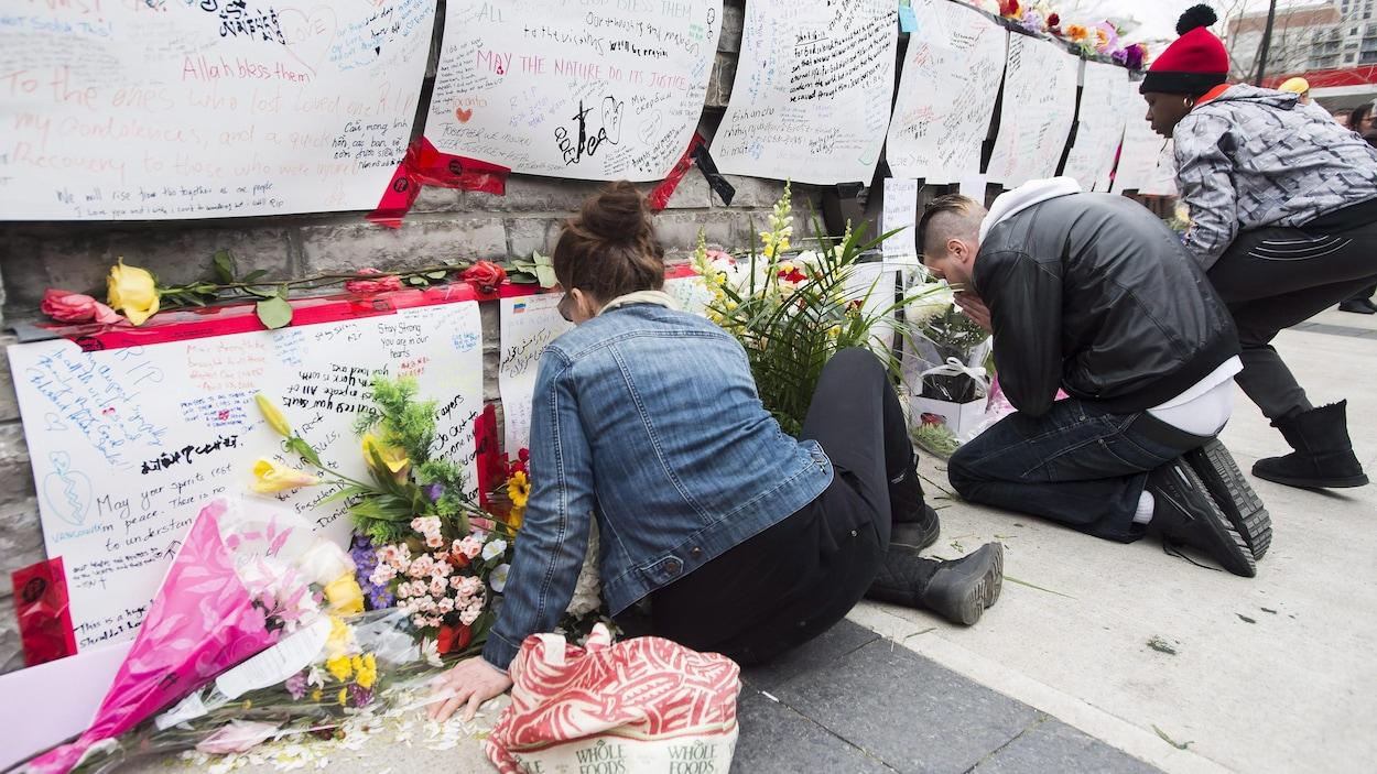 Des gens lisent les messages laissés au mémorial dans un parc du nord de Toronto.