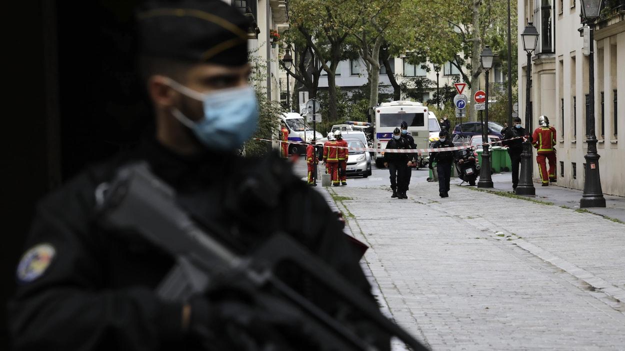 Un gendarme tient une mitraillette et bloque l'accès à la scène de crime.