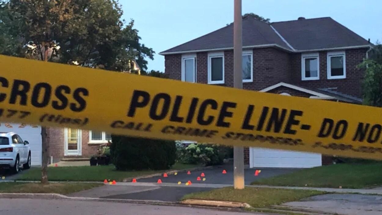 Une banderole de police jaune devant une maison en briques à deux étages.