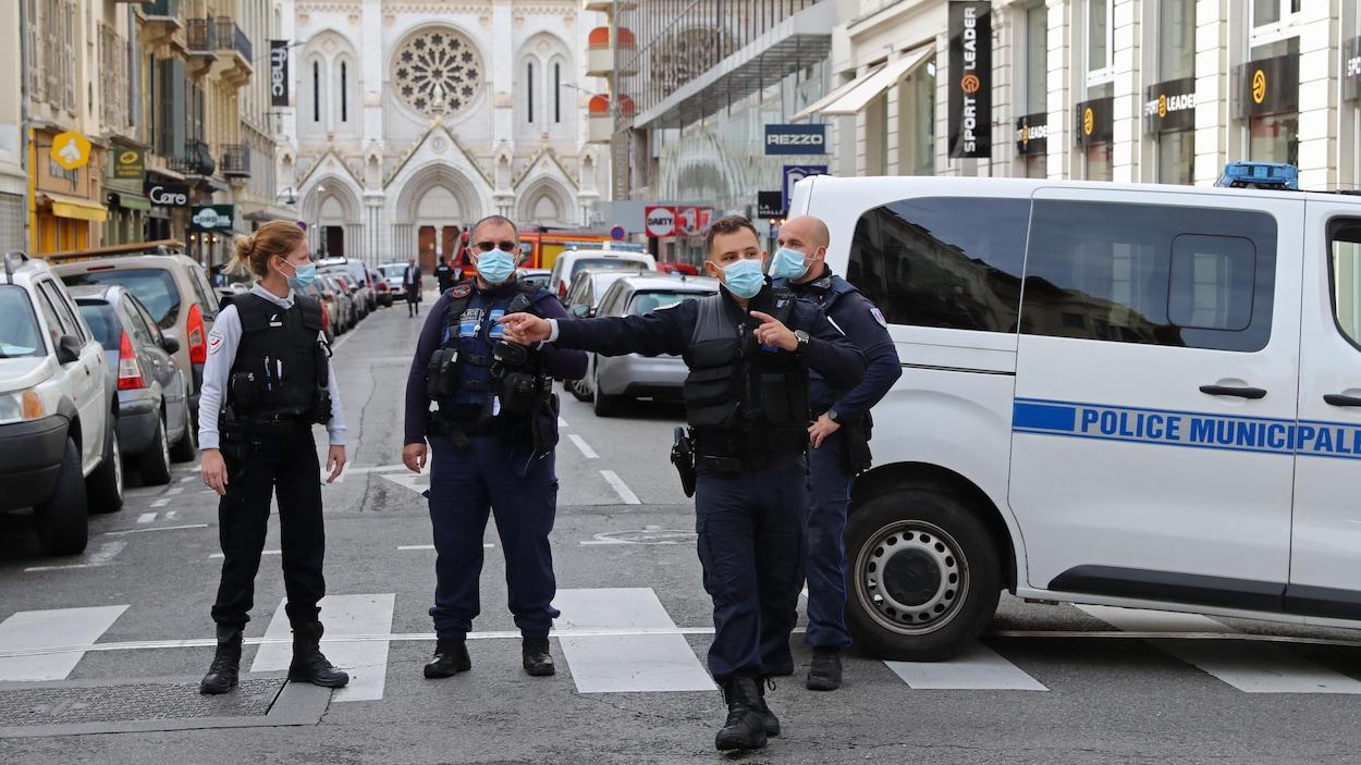 Quatre policiers se tiennent dans la rue.