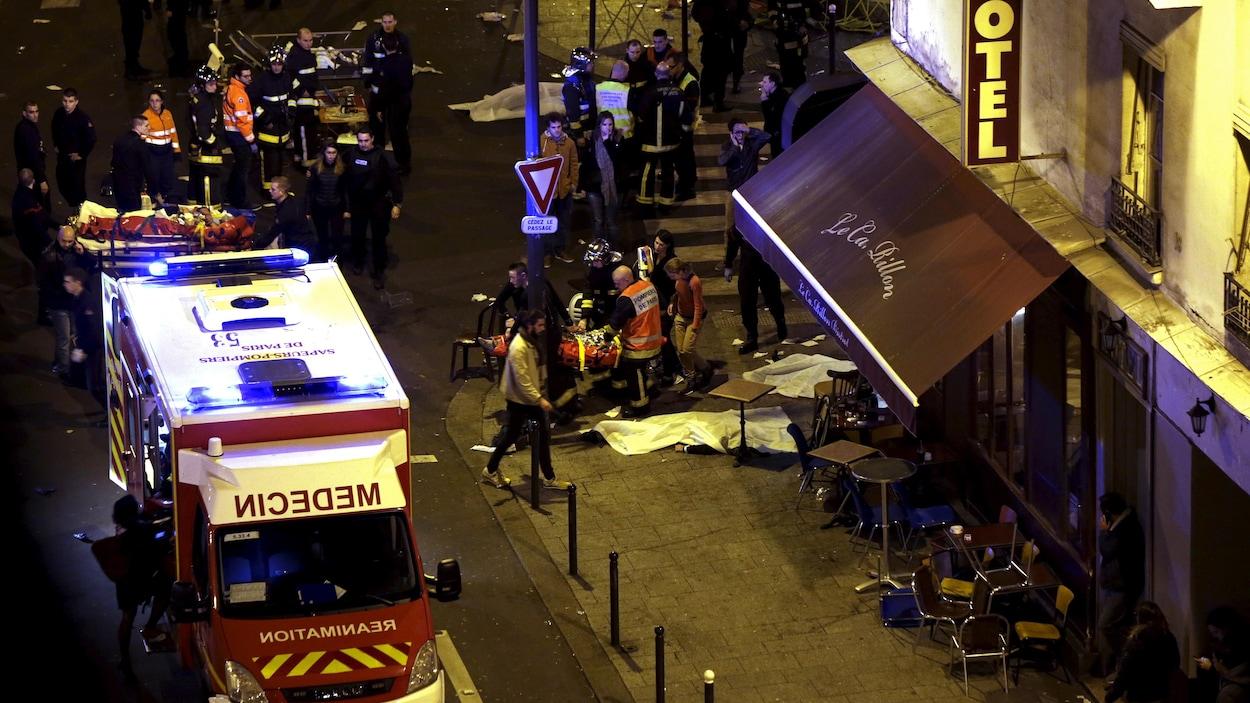 Vue d'ensemble d'un coin de rue où des policiers et des secouristes s'affairent autour d'un camion de pompiers, quelques bâches cachant des corps.